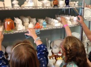 Children choosing pottery to paint