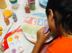 Girl painting an Easter pottery plate in ceramics class