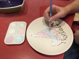 hand painting pottery plate that says believe on it