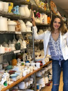 Agi Shah, Owner of Amaze In Pottery Standing by shelves of pottery
