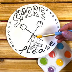 Person painting a plate featuring s'mores