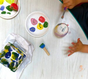 Children painting pottery from a pallette of colors